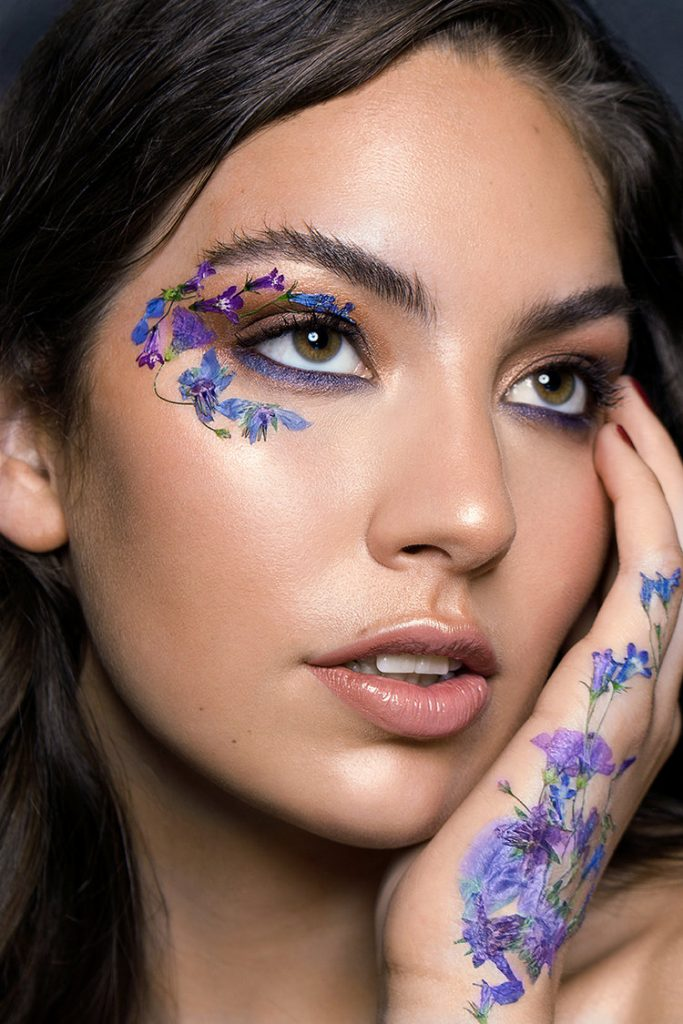 Dimitra Lyras with purple and blue flowers on her face.