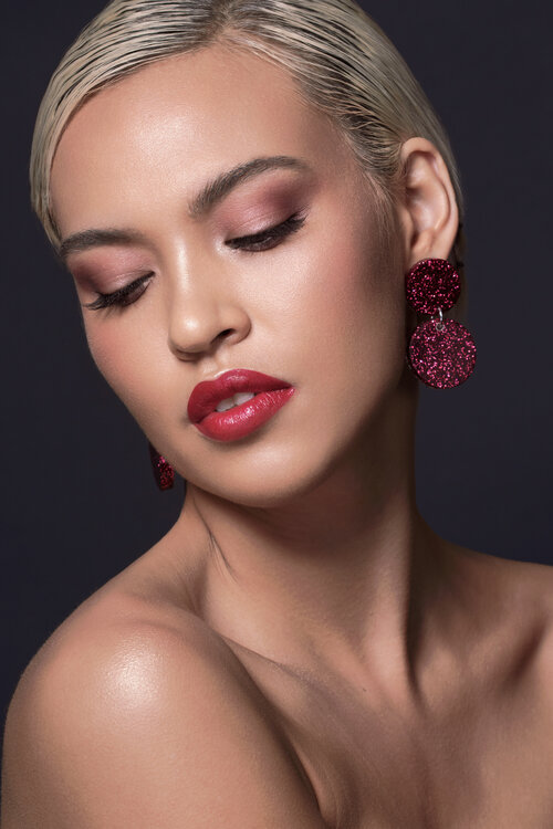 Sinead Carpenter wearing red glitter earrings with a red lip and soft pink eyes.